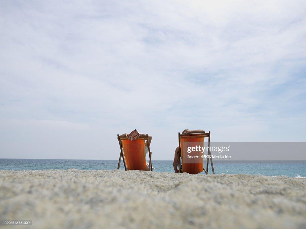 Couple in deckchairs on beach : Stock Photo