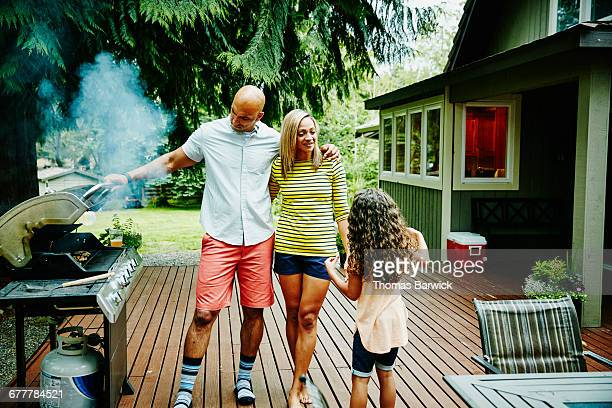 Couple in discussion with daughter in backyard