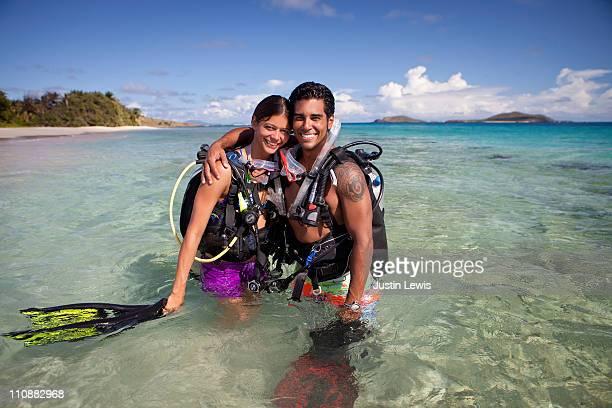 Couple in dive gear hugging in water.