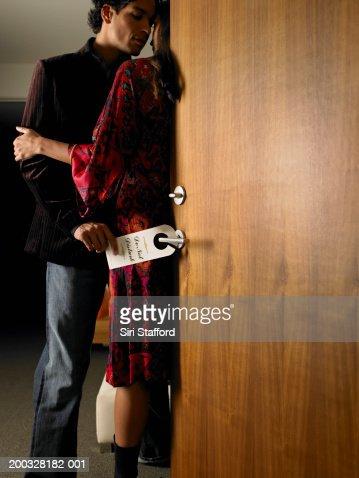 Couple in doorway, man putting 'Do Not Disturb' sign on door handle