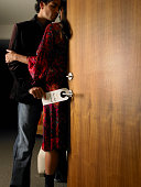 Couple in doorway, man putting 'Do Not Disturb' sign on door handle
