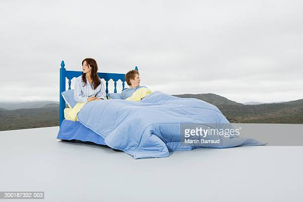 Couple in double bed on platform in rugged landscape, looking to sides
