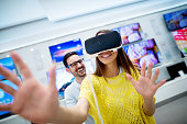 Couple in electronics store, exploring VR goggles.
