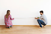 Couple in empty apartment measuring walls