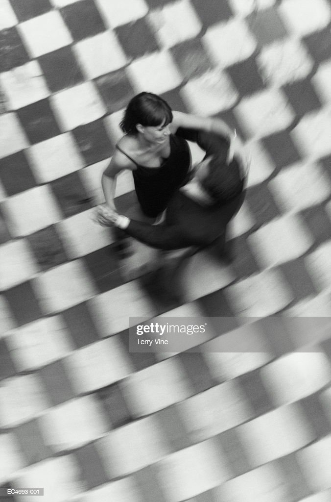 Couple in evening attire dancing on checkered floor, overhead view(B&W