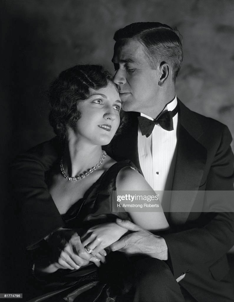 Couple in evening wear, embracing, woman looking up at man, man kissing woman's forehead. : Stock Photo
