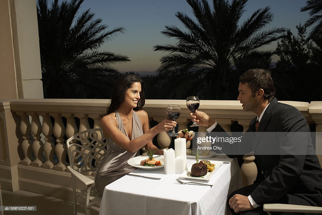Couple in evening wear having dinner on balcony, toasting with red wine
