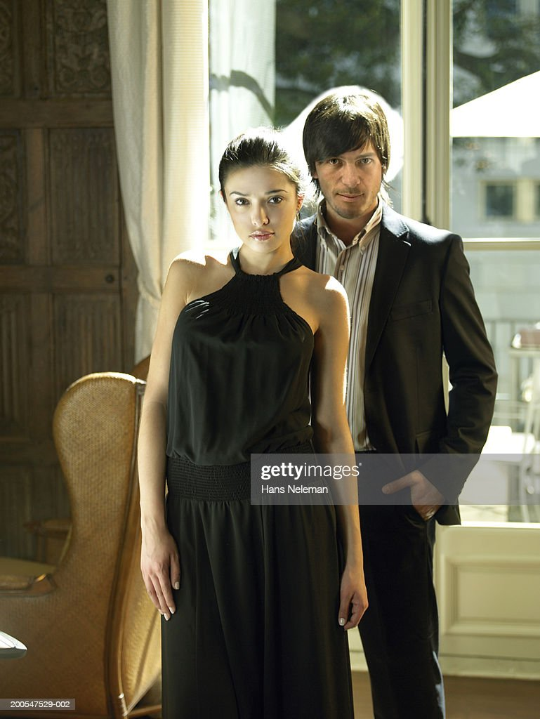 Couple in evening wear in living room, three quarter length : Stock Photo