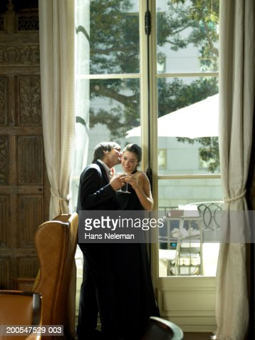 Couple in evening wear with champagne in front of window