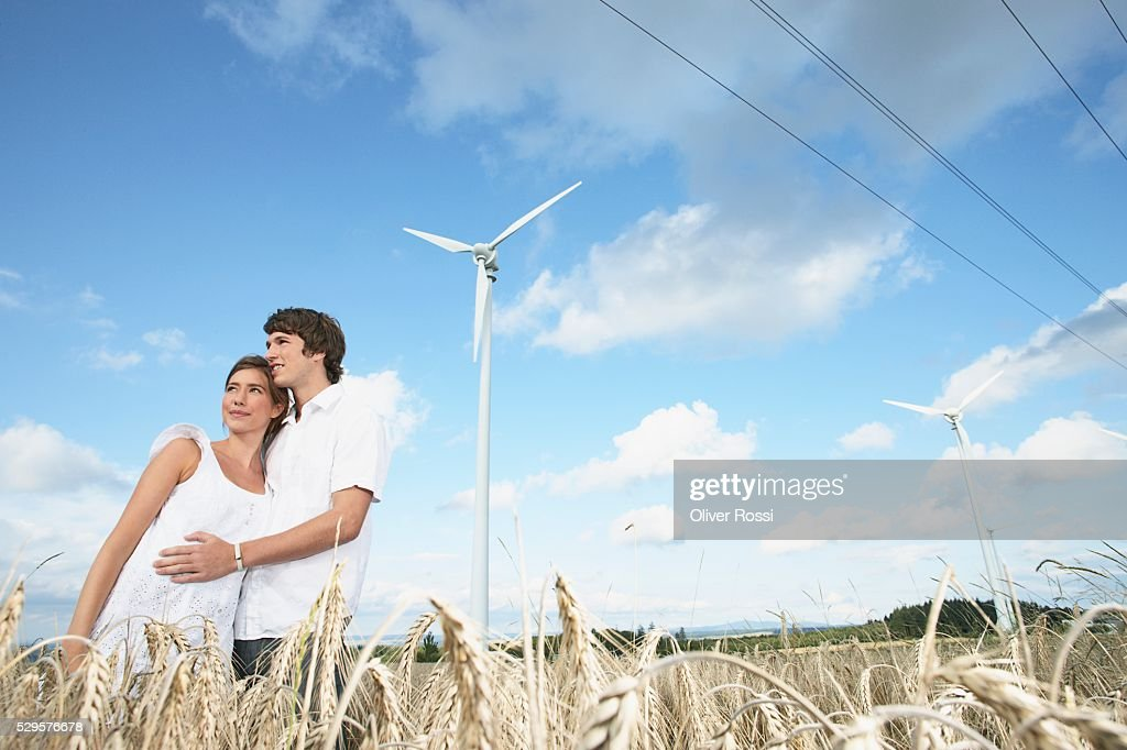 Couple in Field with Windmills : Stockfoto