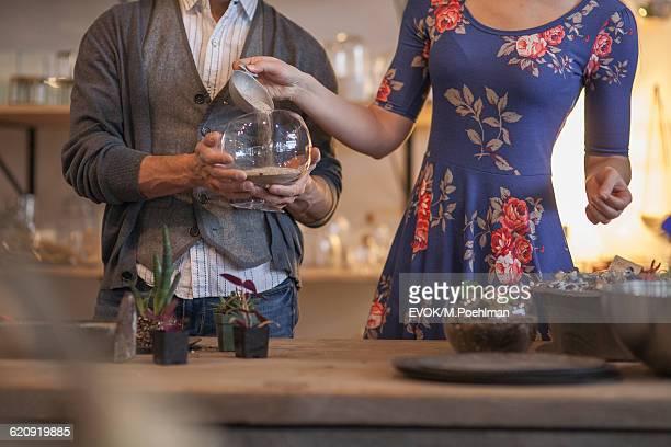 Couple in flower shop making a terrarium at the terrarium bar
