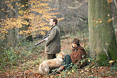 Couple in forest with shotgun and dog, side view