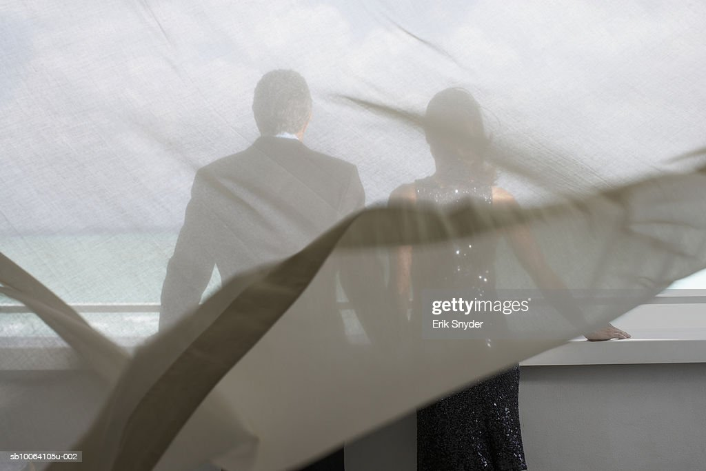 Couple in formal wear on balcony, view through curtain : Stock Photo