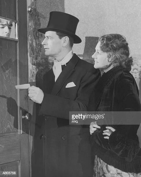 Couple in formal wear showing pass to man at speakeasy door (B&W)