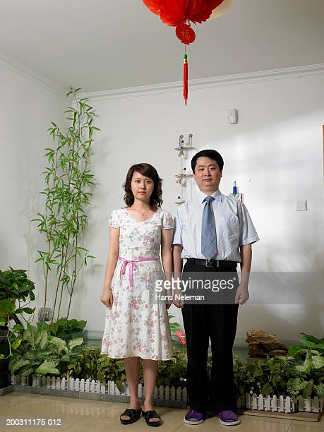 Couple in front of goldfish pool, portrait