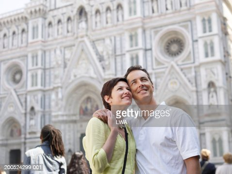 Couple in front of gothic church, looking up : Stock Photo