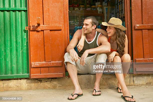 Couple in front of store looking away, smiling