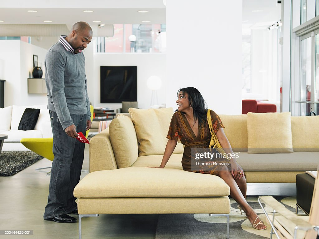 Couple in furniture store, man looking at price of sofa, side view
