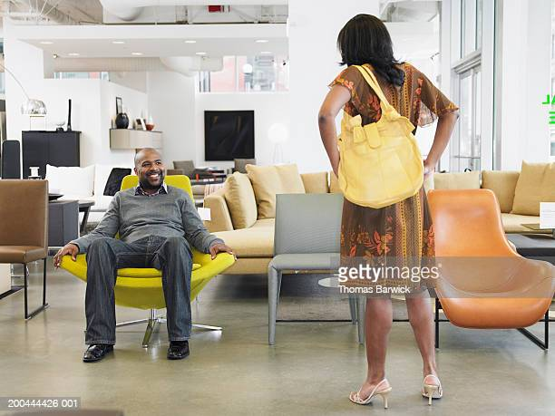 Couple in furniture store, man smiling