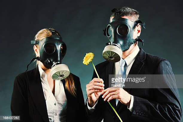 Couple in gas masks with yellow flower