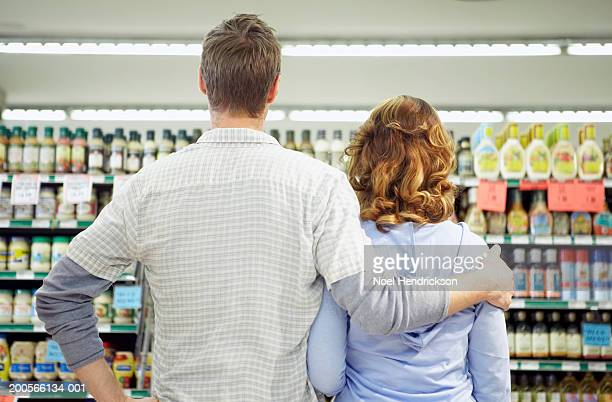 Couple in grocery store looking at shelf of products, rear view