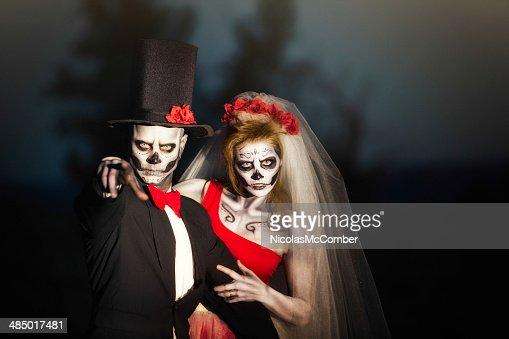 Couple in Halloween skeleton bridal costume does threatening gesture