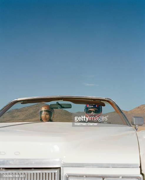 Couple in helmets driving in convertible, close-up