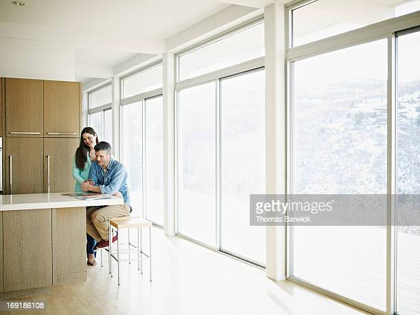 Couple in home smiling looking at digital tablet