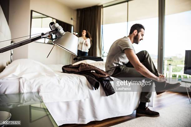 Couple in hotel room getting dressed