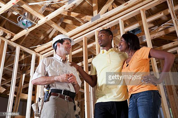 Couple in house under construction with builder