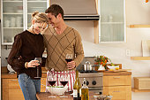 Couple in kitchen holding glasses of wine, heads together, smiling