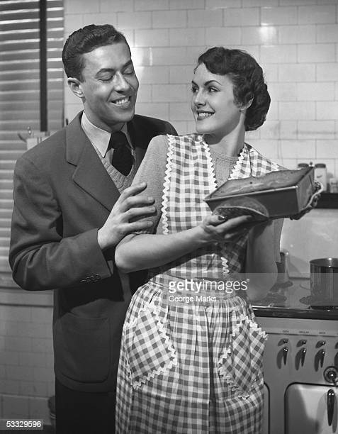 Couple in kitchen looking at cake