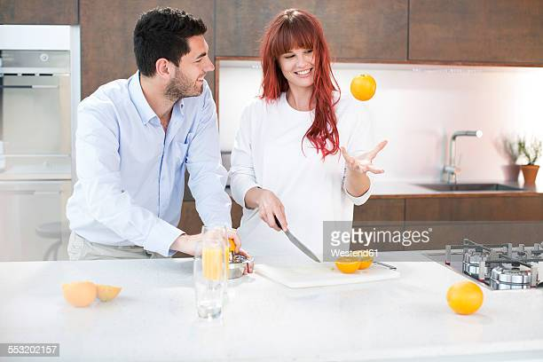 Couple in kitchen making fresh orange juice
