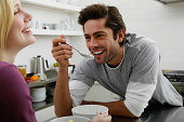 Couple in kitchen, man holding spoonful of food, laughing