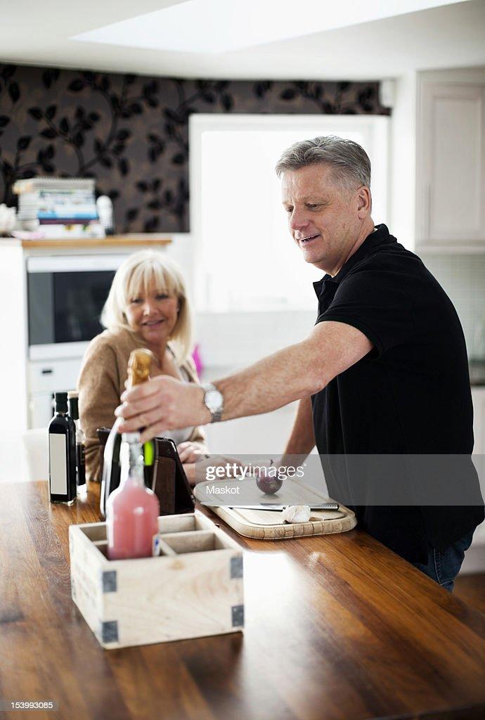 Couple in kitchen preparing food : Stock Photo