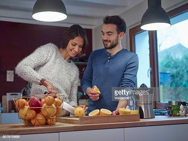 Couple in kitchen slicing oranges for freshly squeezed orange juice
