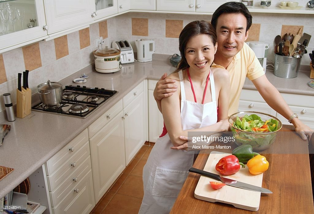 Couple in kitchen, smiling at camera, portrait : Stock Photo