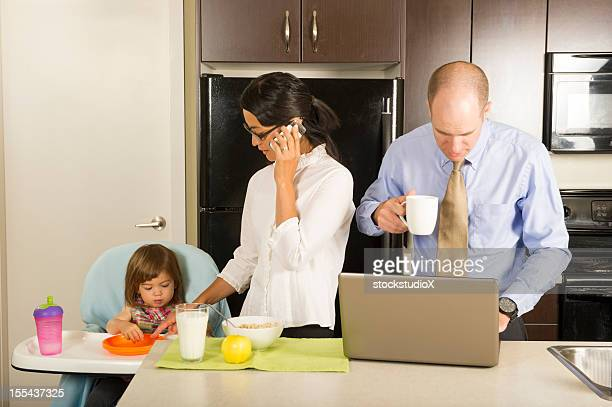 Couple in kitchen starting the day and feeding daughter