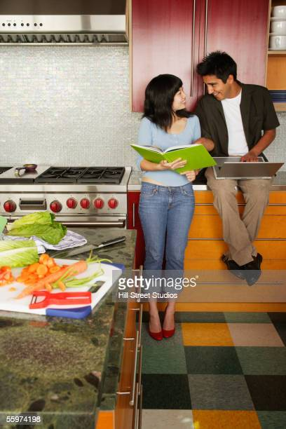 Couple in kitchen using laptop
