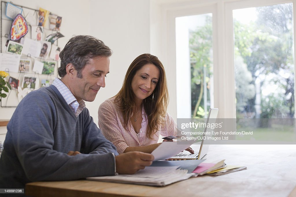 Couple in kitchen with laptop and paperwork : Stock Photo