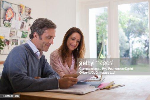 Couple in kitchen with laptop and paperwork : Bildbanksbilder