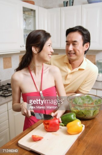 Couple in kitchen, woman chopping vegetables, looking over shoulder, smiling at man : Stock Photo