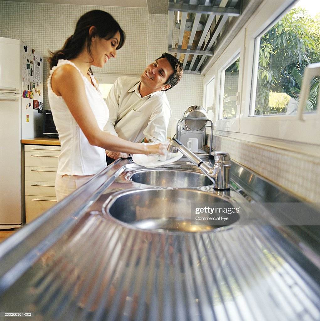 Young woman washing dishes in kitchen by andersen ross photography for - Keywords