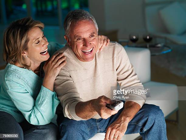 Couple in living room watching television and laughing