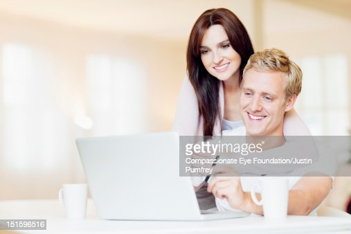 Couple in living room with laptop and credit card : Stock Photo