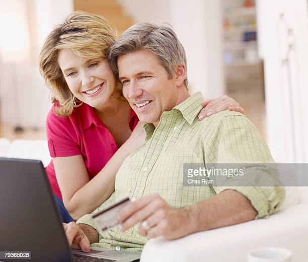 Couple in living room with laptop and credit card