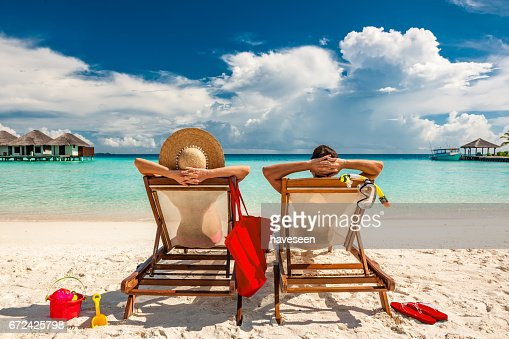 Couple in loungers on beach at Maldives : Stock Photo