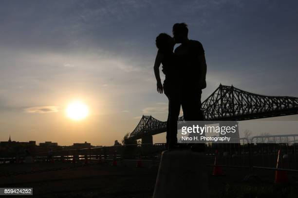 Couple in love at sunset and in the background Jacques Cartier Bridge - Montreal