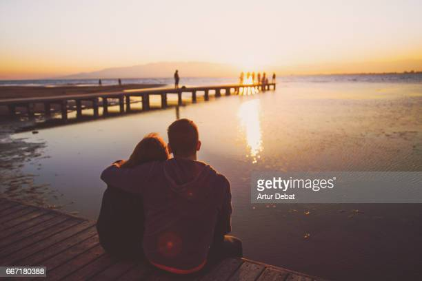 Couple in love during romantic weekend traveling together, sitting in the wood pier contemplating the sunset over the Ebro Delta in the Mediterranean Sea with beautiful colors.