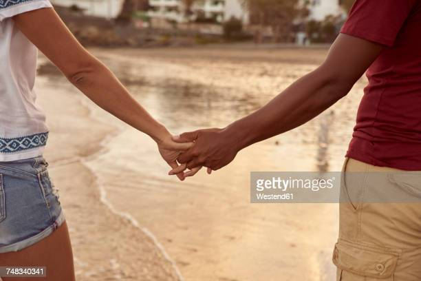 Couple in love holding hands on the beach on the beach, close-up